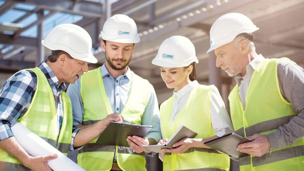 Groupe d'ingénieurs sur chantier avec casque de sécurité